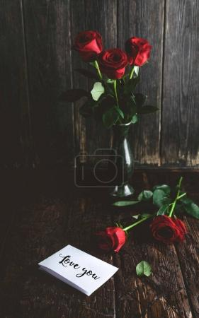 Red roses in vase and Love you greeting card on shabby wooden background, valentines day concept