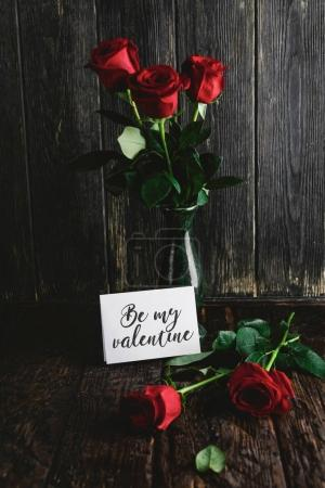 Photo for Red roses in vase and Be my valentine card on shabby wooden background - Royalty Free Image