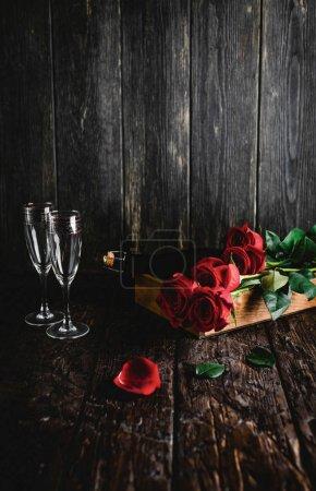 Photo pour Roses rouges et bouteille de champagne et verres sur plateau, Valentin concept - image libre de droit