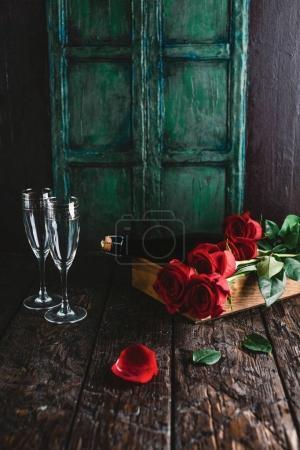 Foto de Rosas rojas y botella de champagne y copas sobre fondo de madera cutre, concepto de día de San Valentín - Imagen libre de derechos