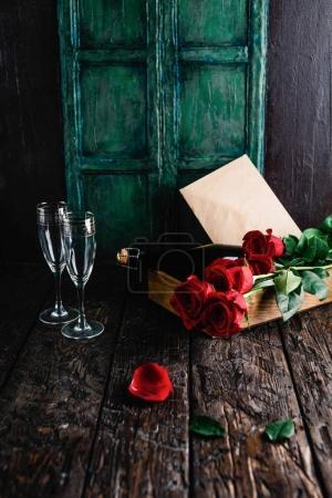 Foto de Rosas rojas y botella de champagne, vasos y sobres en la bandeja, concepto de día de San Valentín - Imagen libre de derechos