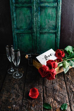 Photo pour Love card, red roses and champagne bottle with glasses on shabby table, valentines day concept - image libre de droit