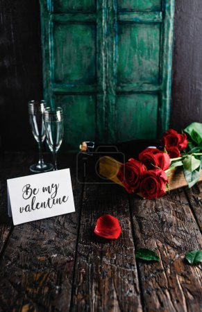 Photo pour Be my valentine greeting card, red roses and champagne bottle with glasses on shabby table - image libre de droit