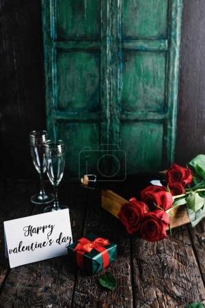 Photo for Happy valentines day greeting card, present, red roses and champagne bottle with glasses - Royalty Free Image