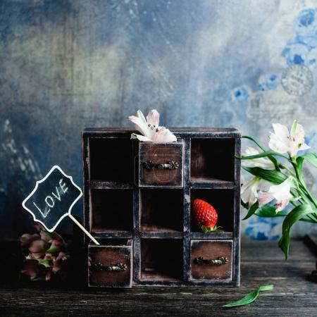 Photo for Little vintage cabinet with flowers, strawberry and love sign for valentines day - Royalty Free Image