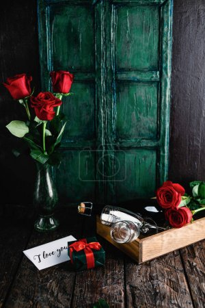 Photo pour I love you greeting card, gift, red roses and champagne bottle with glasses for valentines day - image libre de droit