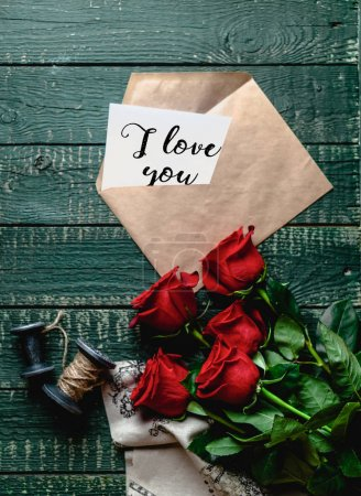 top view of red roses and envelope with I love you valentine card on wooden background
