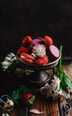 Photo pour Bol avec fraises sur table en bois avec fleurs et bouteille de champagne et macarons - image libre de droit
