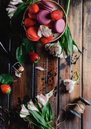 Photo pour Vue de dessus des fraises et macarons sur table en bois avec bouteille de champagne pour la Saint Valentin, les fils et les fleurs - image libre de droit
