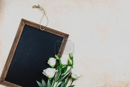 Photo for Top view of blackboard in wooden frame with eustoma flowers on shabby background - Royalty Free Image