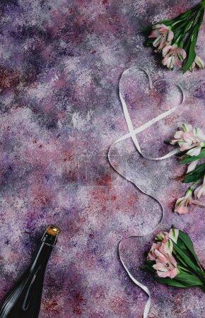 Photo pour Vue de dessus de bouteille de champagne, fleurs et coeur en forme de ruban violet sur table, concept de Saint Valentin - image libre de droit