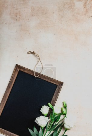 Photo for Top view of wooden frame with eustoma flowers on shabby background - Royalty Free Image