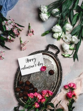 Foto de Vista superior de la bandeja antigua con caramelos de chocolate, flores y feliz día de San Valentín tarjeta de felicitación - Imagen libre de derechos