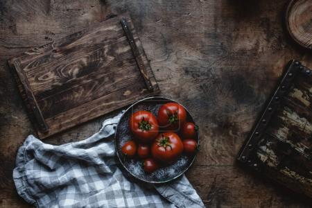 Photo for Top view of ripe tomatoes on plate on wooden tabletop - Royalty Free Image