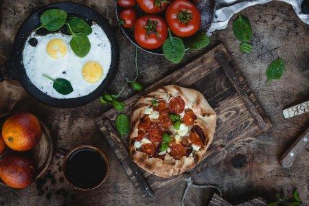 Photo pour Vue de dessus de boulangerie savoureuse avec tomates sur plateau en bois, oeufs frits, tomates fraîches et germes sur table - image libre de droit