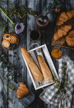 Photo for Top view of loafs of bread in wooden box with croissants and drink around on wooden tabletop - Royalty Free Image