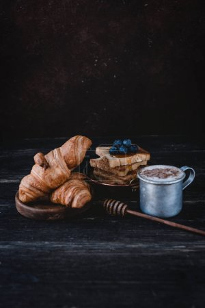 Photo for Close up view of croissants, toasts with blueberries and drink on wooden tabletop - Royalty Free Image