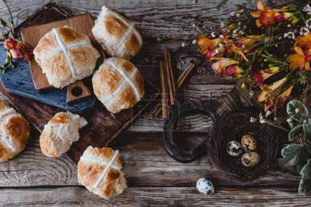 Photo pour Petits pains croisés chauds sur la table avec des fleurs et des œufs de caille - image libre de droit
