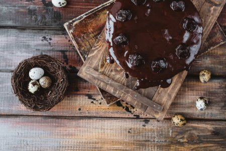 Photo for Quail eggs in nest and chocolate cake on rustic wooden table - Royalty Free Image