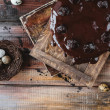 Quail eggs in nest and chocolate cake on rustic wooden table