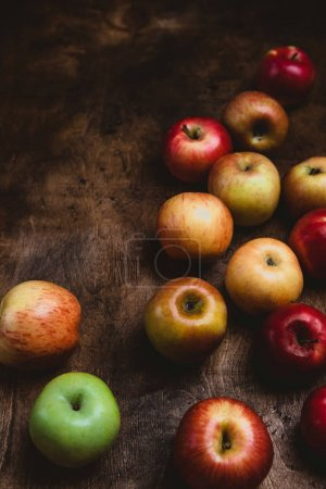 Photo for Closeup shot of pile of apples on rustic wooden table - Royalty Free Image