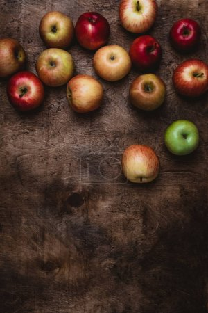 top view of different apples on rustic wooden surface