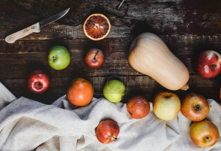 top view of pumpkin, apples, blood oranges, kitchen towel and knife on wooden table