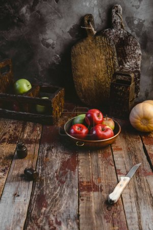 cutting boards, grater, pumpkin, plate with apples and knife on wooden table