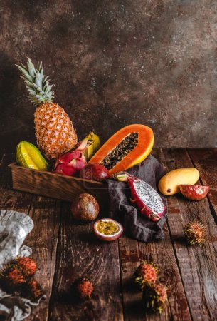 Photo for Carambolas, papayas, pineapple, rambutans, passion fruits and mango on wooden tabletop - Royalty Free Image