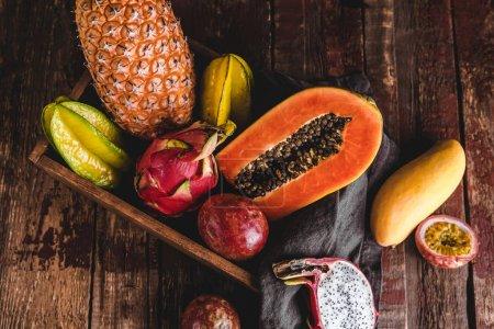 Foto de Vista superior de carambolas, papayas, piña, rambutanes, maracuyá y mango sobre mesa de madera - Imagen libre de derechos