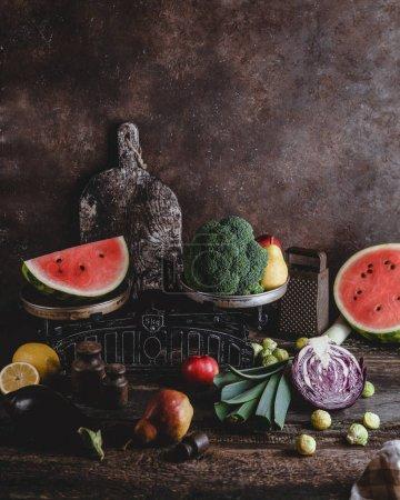 Schneidebrett, Reibe, Waage, verschiedene Obst- und Gemüsesorten auf rustikalem Holztisch