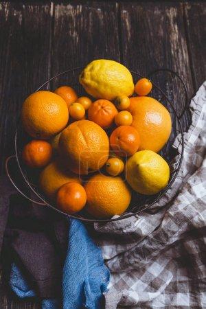 Photo pour Vue de dessus des oranges, mandarines, citrons, kumquats en plaque et cuisine serviettes sur la table en bois - image libre de droit