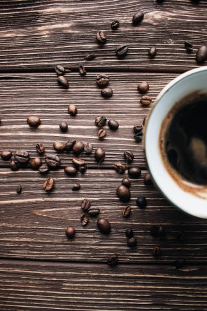 cup of black coffee and coffee beans on dark background