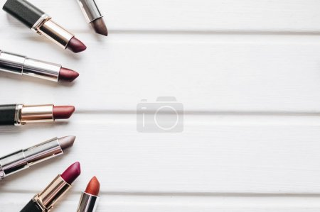Lipsticks of different colors on wooden background