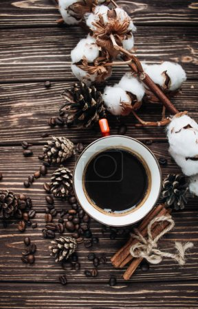 close-up view of roasted coffee beans, cup of coffee, cotton flowers, cinnamon and pine cones