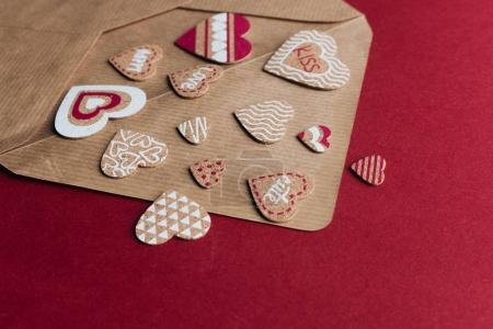 Valentines day craft envelope with decorative handmade hearts on red background