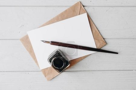 set of vintage dip pen, inkpot and blank paper sheet with envelope on white wooden table