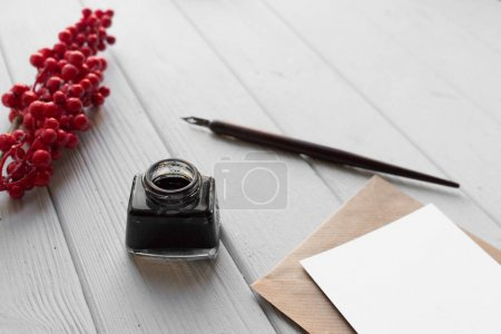 set of vintage dip pen, inkpot, blank paper sheet with envelope and red berries on white wooden table