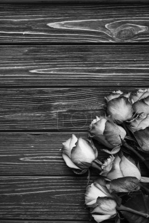 beautiful roses bouquet on wooden planks background, black and white