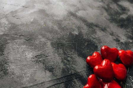 Photo pour Pile de cœurs rouges décoratifs sur fond de pierre sombre, concept Saint Valentin - image libre de droit
