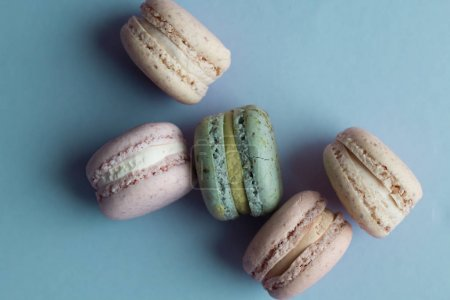 composition of delicious colorful macaroons on blue table, sweet dessert