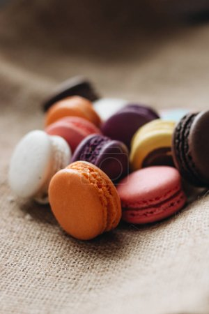 composition of delicious colorful macaroons on sackcloth, sweet dessert