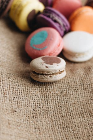 composition of delicious colorful macaroons on sackcloth sweet dessert