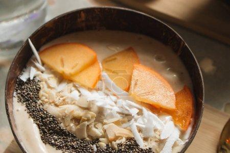 Photo pour Bol avec persimmon tranché, noix et graines de - image libre de droit