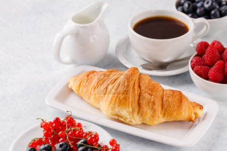 Photo for Breakfast of oatmeal with berries, coffee with croissants, blue background, horizontally - Royalty Free Image