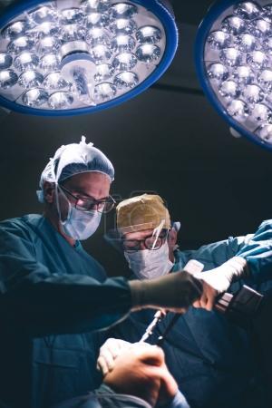 Doctors operating kneecap.