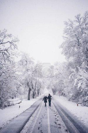 Couple walks on snowy road.