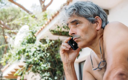 Attractive white hair man speaks with mobile phone.