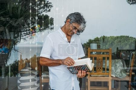 Attractive white hair man reads a book in his country house.