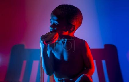 Silhouette african boy eats red blue hamburger.